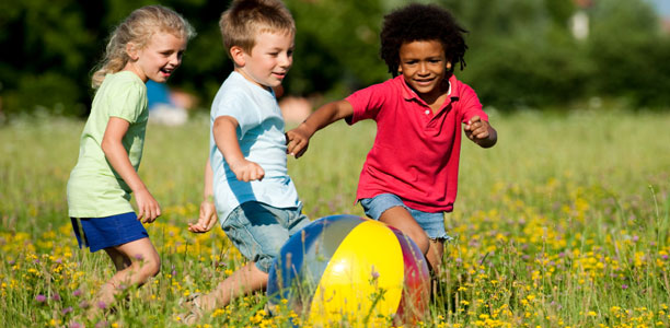 kids-chase-ball-in-summer
